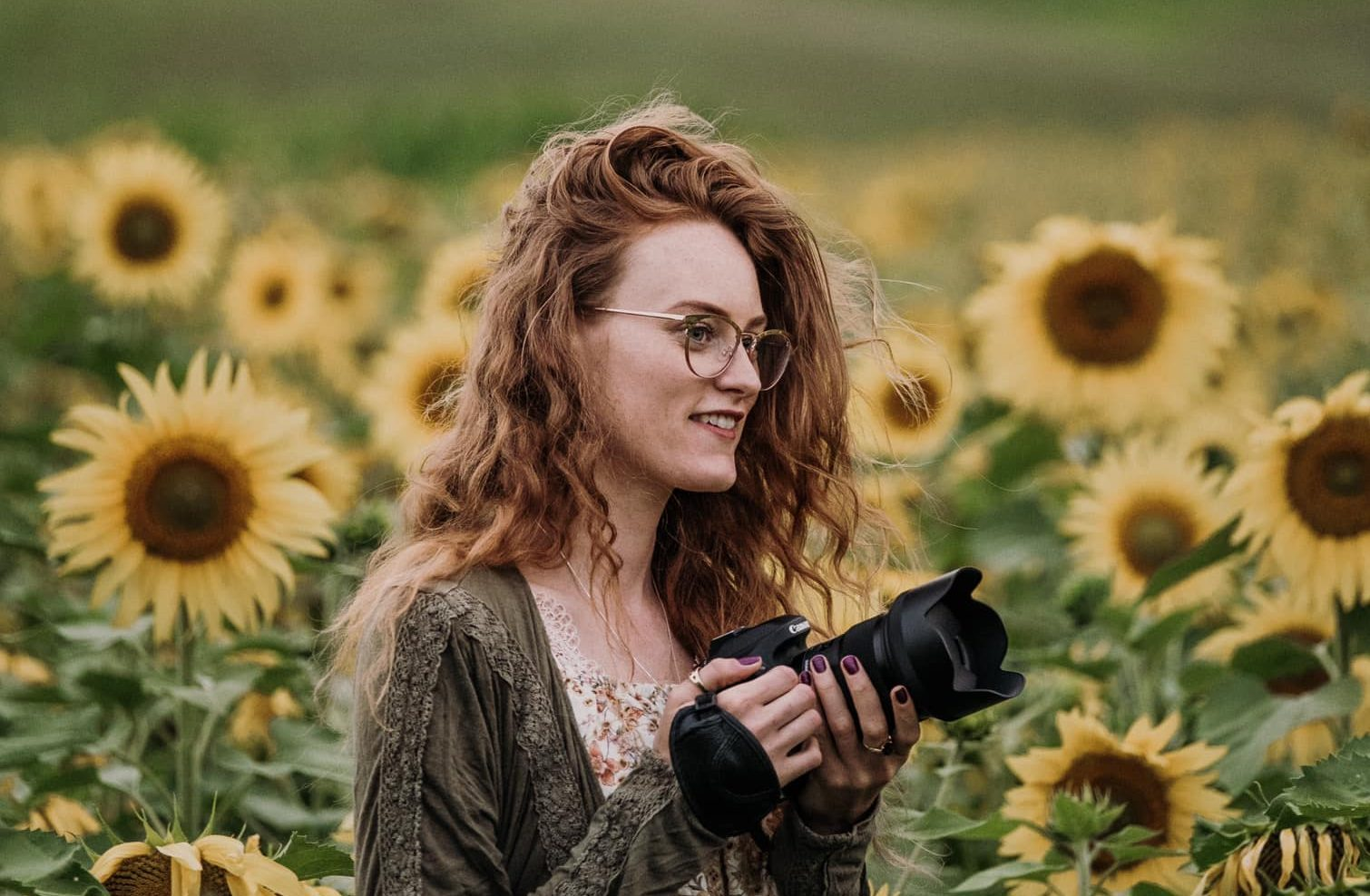 photographer with camera in a sunflower field