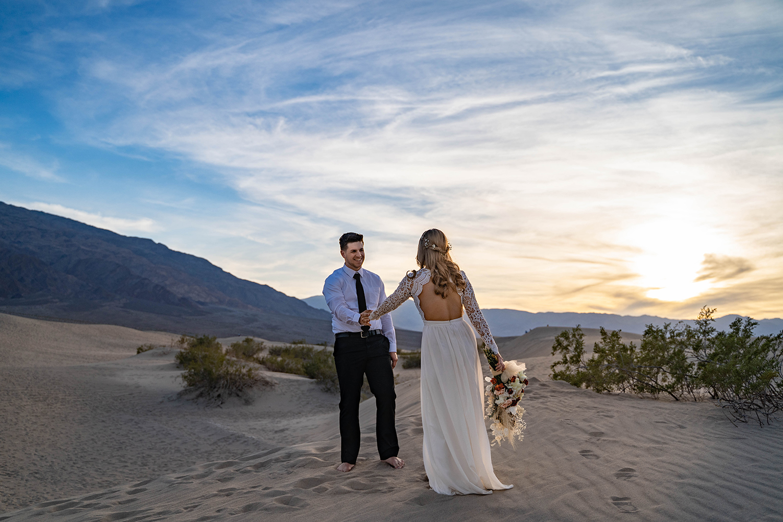 groom leading bride through Mesquite Sand Dunes