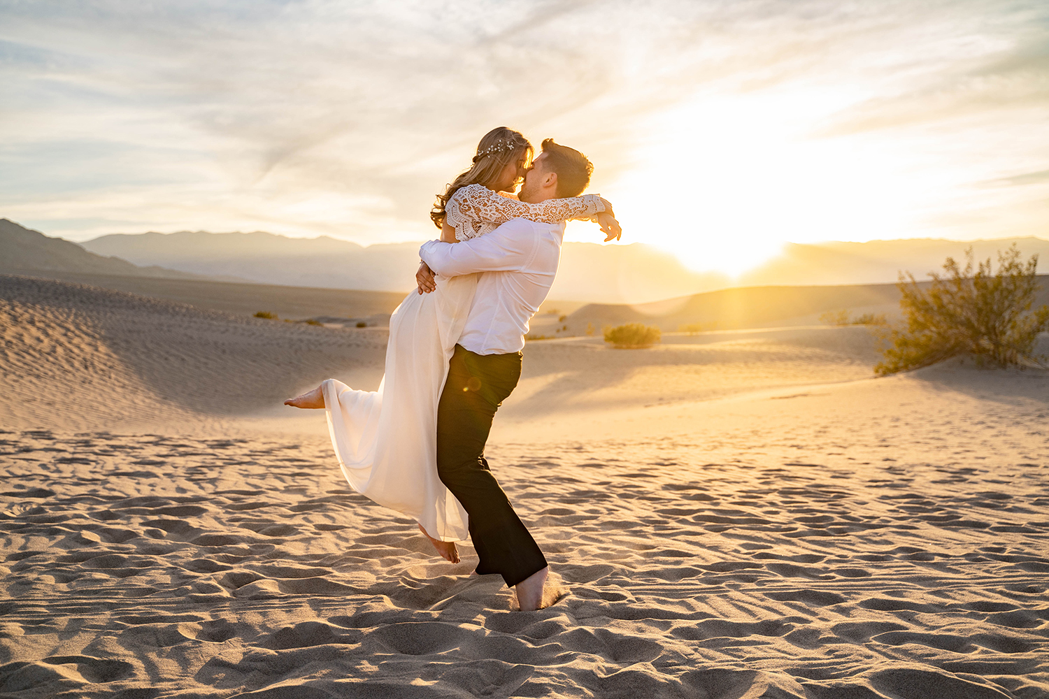 groom picking bride up for kiss at sunset
